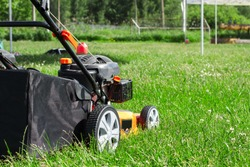 The lawn mower with a grass collector is ready to work