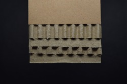 The 5-layer corrugated cardboard consists of two layers of corrugated and three flat board on black background.