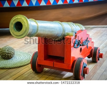 The layout of the gun on a wooden carriage. Decorative gun and core. Model guns on a wooden floor. Demonstration of ancient weapons. History of weapons. Toy gun. #1472222318
