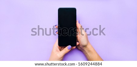 The layout of the phone. The girl holds the phone with both hands. Background lilac under the color of nails. A beautiful manicure. Flat lay.