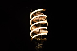 The LED filament of a vintage style bulb, with a warm light.  The low light intensity makes the filament really visible.