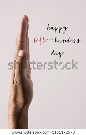 the left hand of a young man and the text happy left-handers day against a beige background