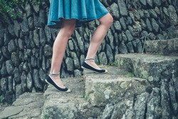 The legs and feet of a young woman walking up some steps outside