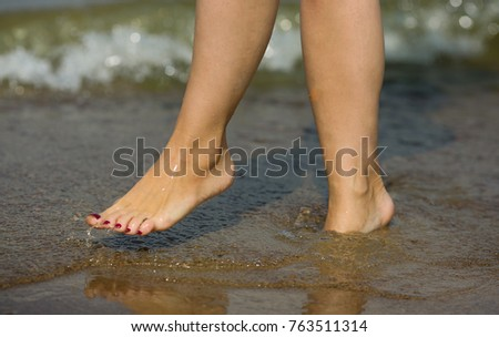 The legs of a girl walking along the sandy bottom of the sea against a background of waves. People, lifestyle, leisure and relaxation  #763511314