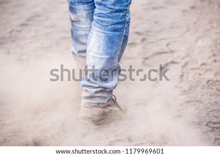 The legs of a man in jeans and boots are walking along a dusty road. A working man goes to a factory or a construction site. Industrial harmful for the environment and health work.