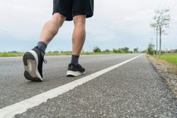 The legs of male athletes in black shoes are preparing to run on the paved road Outdoor exercise for weight loss and good health.Fitness and healthy lifestyle Competition and successful concept.