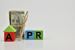 the letter APR printed on a wooden block, refers to the Annual Percentage Rate which is the interest rate charged in financing a housing loan. There is a dollar bill on the back of the wooden block.