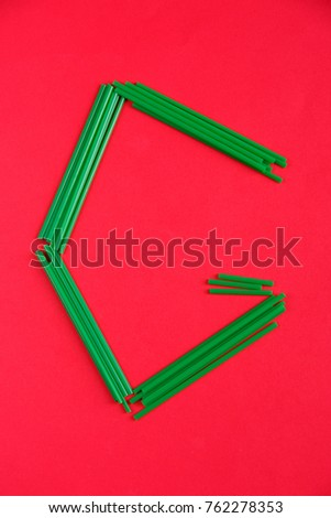 The letter G of green color, is laid out of cocktail tubes on a red background. #762278353