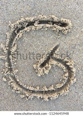 The letter G of the alphabet writing on the beach sand  #1124645948