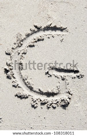 The letter G of the alphabet writing on the sand beach