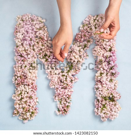 The letter M of the Roman english alphabet, the Russian alphabet is lined with lilac flowers hand made on a blue background #1423082150