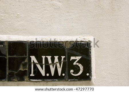 The letter N E W from tiled street sign on white wall London England UK