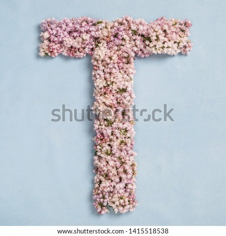 The letter T of the Roman english alphabet, the Russian alphabet is lined with lilac flowers on a blue background #1415518538