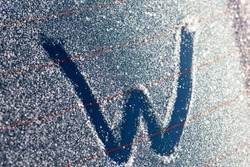 the letter w drawn from the beginning of the word winter on the car window in the winter season, cold winter weather and details of the car window with the drawn letter