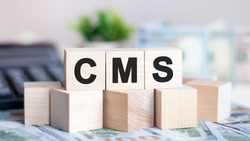 The letters cms written on wood cubes. banknotes, calculator and green plant in a flower pot on the background. cms - short for content management system, business concept.