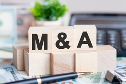 The letters M and S written on wood cubes. Pen, banknotes, calculator and green plant in a flower pot on the background. M and A - short for Mergers and Acquisitions, business concept.