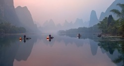 The Li River, Xingping, China, scenic landscape. Cormorant fishermans on the ancient bamboo boats with a lighted lamps at sunrise.