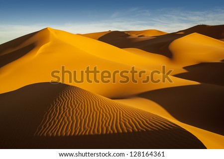 The Libyan desert - a fantastic place for travelers and photographers. Rocks of an unusual form, beautiful structure of dense yellow sand, dune of the huge sizes and deep sky of Sahara. #128164361