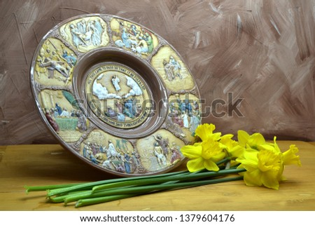The life of Jesus Christ in pictures on a clay plate, yellow daffodils lie on a wooden table