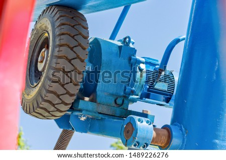 """The lifting mechanism of the attraction """"Ferris wheel/Ferris wheel"""" close-up. Shaft for lifting and rotating the Ferris wheel #1489226276"""