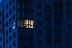 the light burns in one window of the multitude in a multi-storey residential building