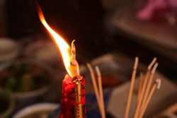 The light of candle and incense on the table food for spirits in Chinese Ghost Festival, focus at the candle and incense, Translation: The business prospered