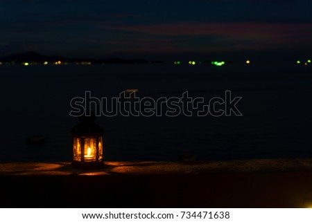 The light or lantern is shining in the dark and placed on the edge of the mortar with sea and twilight sky at night as background. #734471638