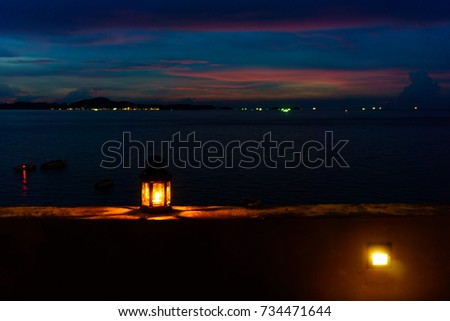 The light or lantern is shining in the dark and placed on the edge of the mortar with sea and twilight sky at night as background. #734471644
