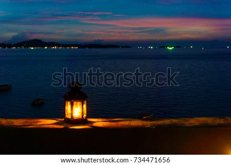 The light or lantern is shining in the dark and placed on the edge of the mortar with sea and twilight sky at night as background. #734471656