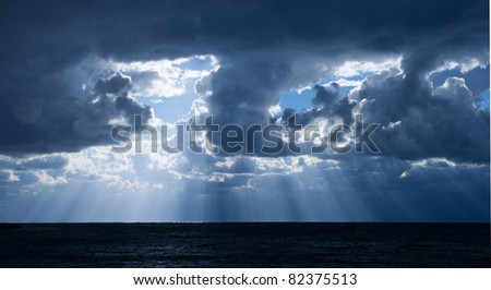 The light rays through the clouds over the sea