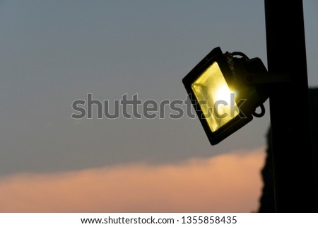 The light that is attached to the pole to illuminate at night and has a yellow light With a warm atmosphere. #1355858435