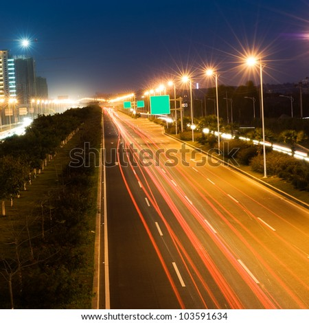 The light trails on the modern building background in urban city of China.