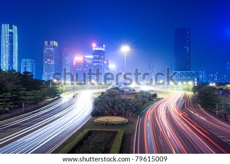the light trails on the street with modern city background at night