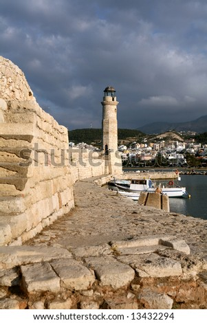 The lighthouse at the Venetian Harbour in Rethymnon, Crete, in evening light, with the city and hills behind.
