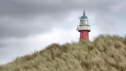 The lighthouse of Scheveningen near the city of the Hague in the Netherlands. The foreground shows a sand dune full of grass and the sky is overcast.