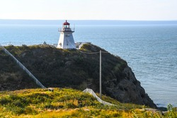 The lighthouse on Cape Enrage, New Brunswick, Canada, on the edge of the rocky angled cliff with fencing and poles at angles