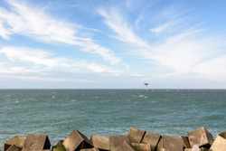 The lighthouse with heliplatform at the entrance of the Port of Rotterdam in the Netherlands. There are concrete wave breakers in the foreground and in the blue sky above are white cirrus clouds.