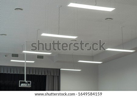 The lighting system in the auditorium. Fluorescent lamps hanging from the ceiling.
