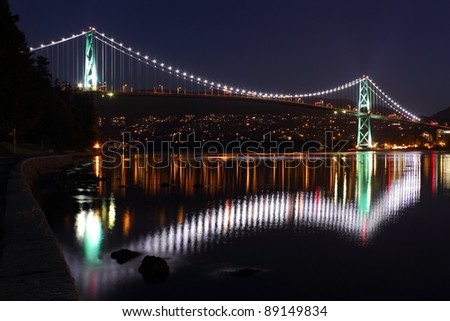 The lights of the Lions Gate Bridge reflect in Burrard Inlet. Seen from the seawall surrounding Stanley Park. Vancouver, British Columbia.