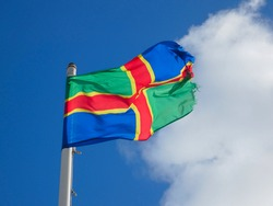 The Lincolnshire flag, a county in the United Kingdom, flying on a very windy day