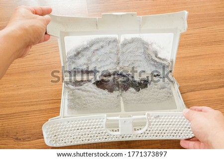 Photo of  The lint trap on the wooden floor which have a lot of lint and fiber, wool from cloths after drying in the dryer machine.