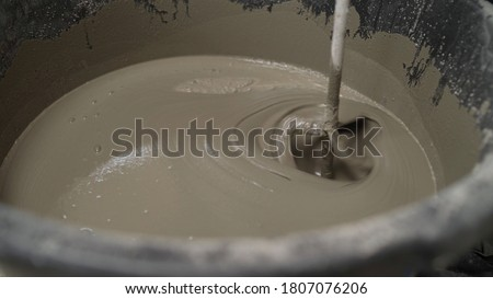 The liquid flooring compound is mixed in a bucket. The mortar is mixed in a bucket. fresh wet mixed cement mortar with trowel inside bucket by close up view Foto stock ©