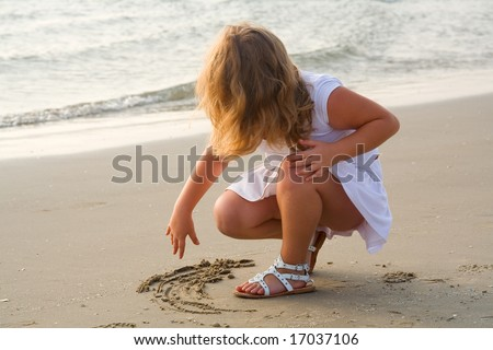 The little beautiful girl the blonde draws on sand on seacoast