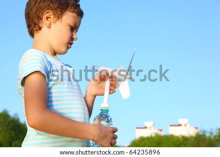 The little boy against the blue sky plays with a wind-driven generator.