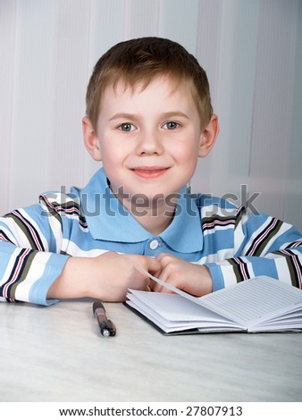 the little boy doing homework on the table