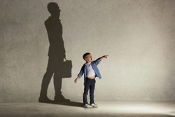 The little boy dreaming about businessman or diplomat profession. Childhood and dream concept. Conceptual image with boy and shadow of man in suit on the studio wall