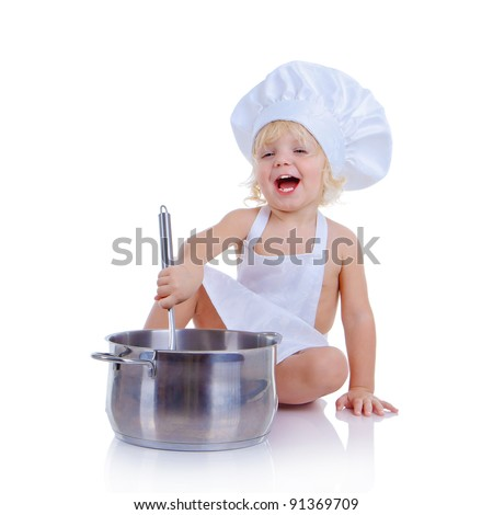 The little boy in a suit of the cook playing with kitchen accessories (isolated on white)