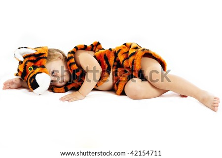 The little boy in a suit of tiger lies on a floor