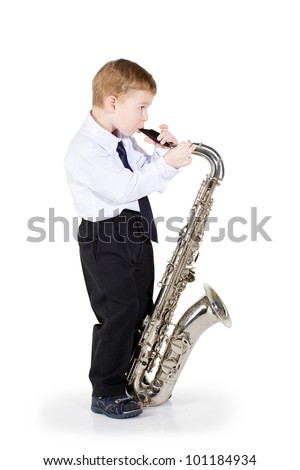 The little boy in black trousers and a white shirt costs with a saxophone in hands