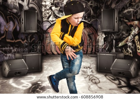 The little boy in the style of Hip-Hop . Children's fashion.Cap and jacket. The Young Rapper.Graffiti on the walls.Cool rap dj.